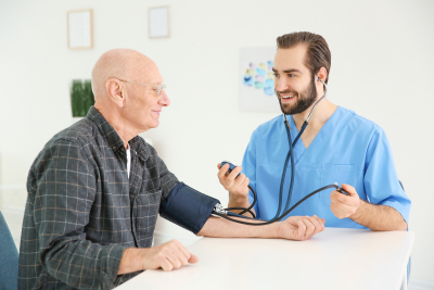 nurse measuring blood pressure of senior man at home