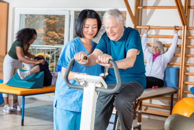 Asian nurse helping elder man in hospital gym
